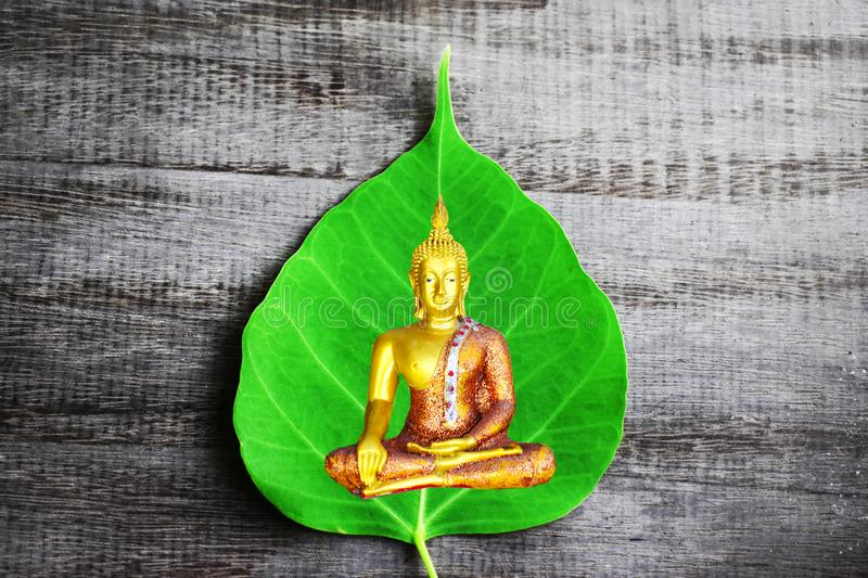 Buddha image and green Bodhi leaf on the old wooden background royalty free stock photo