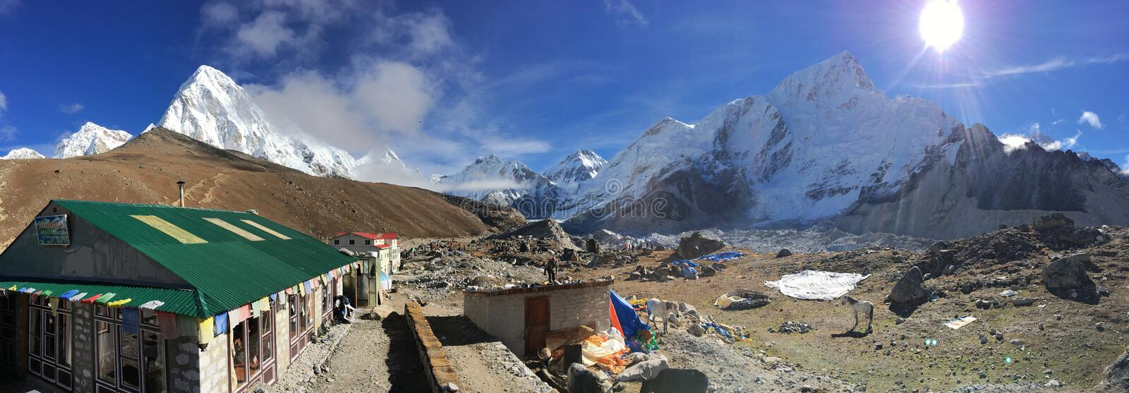 Buddha Lodge & Restaurant at Gorak Shep with snow capped Himalayan range scenery. The sun is shinnig bright and there are horses resting. This specific image is stock image