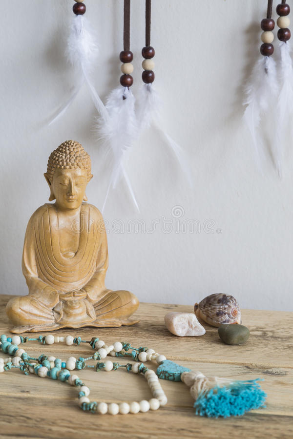 Buddha with Mala. Peaceful tabletop scene with wooden Buddha statue, mala beads and dreamcatcher stock photography
