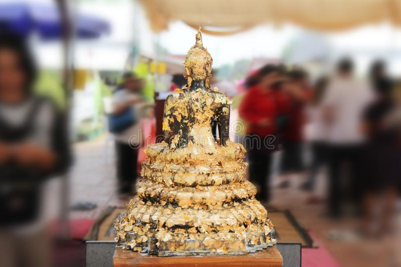 Buddha meditating on a lotus base 5 step. Gilded words surrounding . Photographed from behind royalty free stock photo