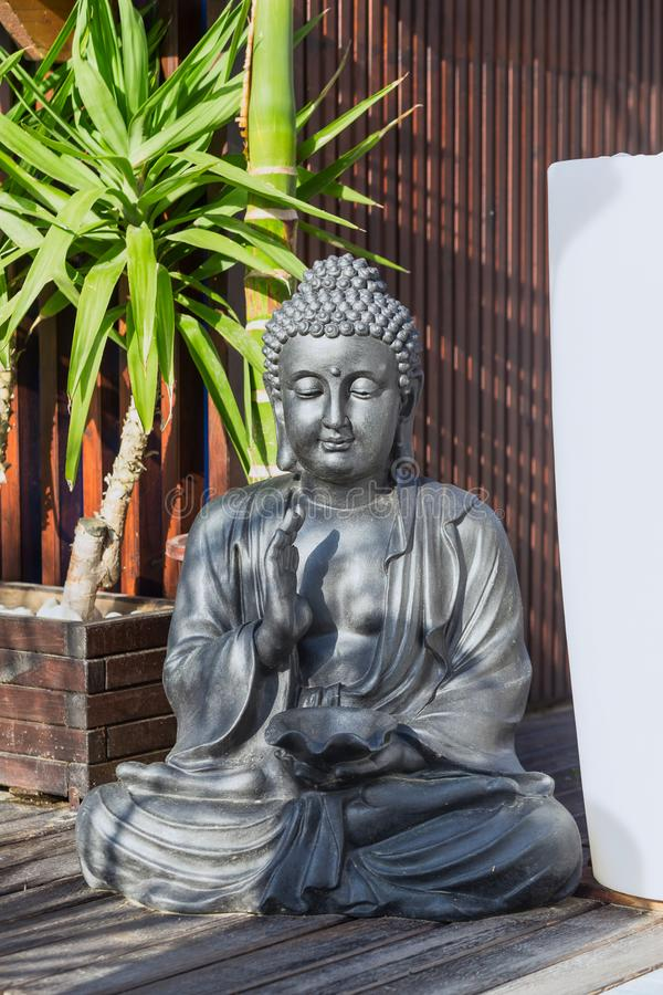 Statue of a meditating Buddha on a background of tropical greenery. stock photo