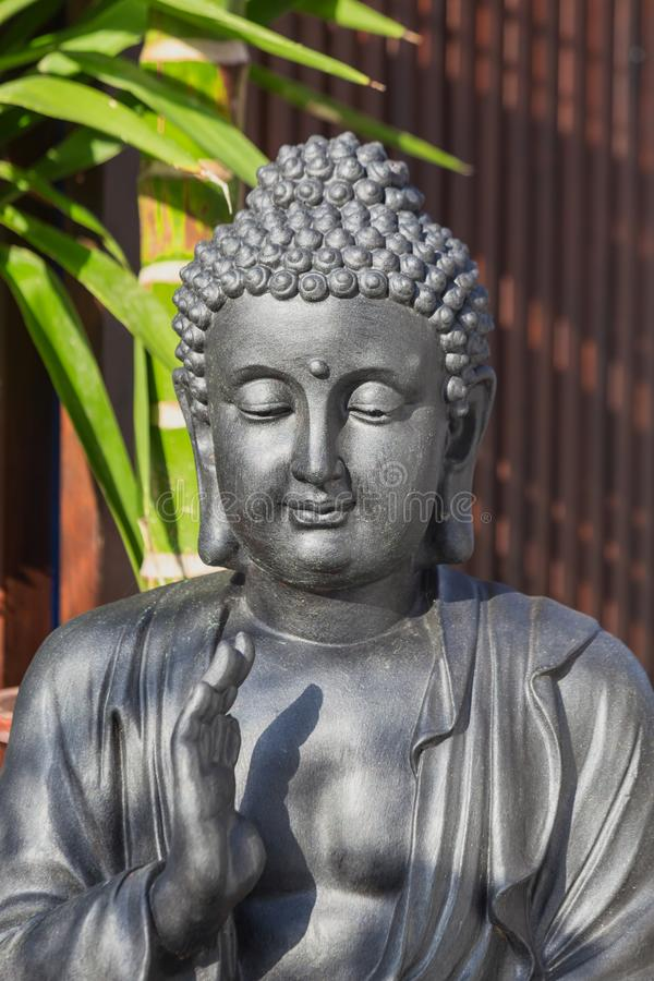 Statue of a meditating Buddha on a background of tropical greenery. Soft focus. stock photo