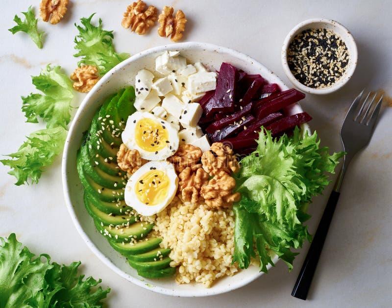 Buddha puchar, zrównoważony jedzenie, jarski menu Popielaty marmuru stół, odgórny widok Jajka, avocado, sałatkowa sałata, bulgur, zdjęcie stock