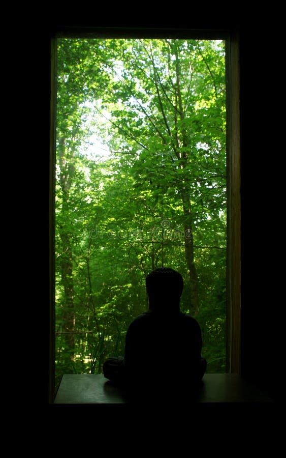 Buddha que mira hacia fuera la ventana fotografía de archivo libre de regalías