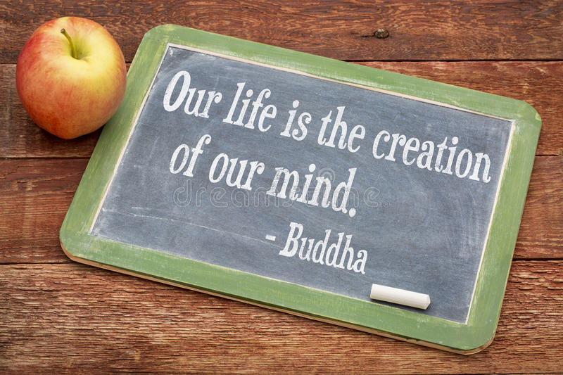 Buddha quote on life. Our life is creation of our mind - Buddha quote on a slate blackboard against red barn wood royalty free stock photos