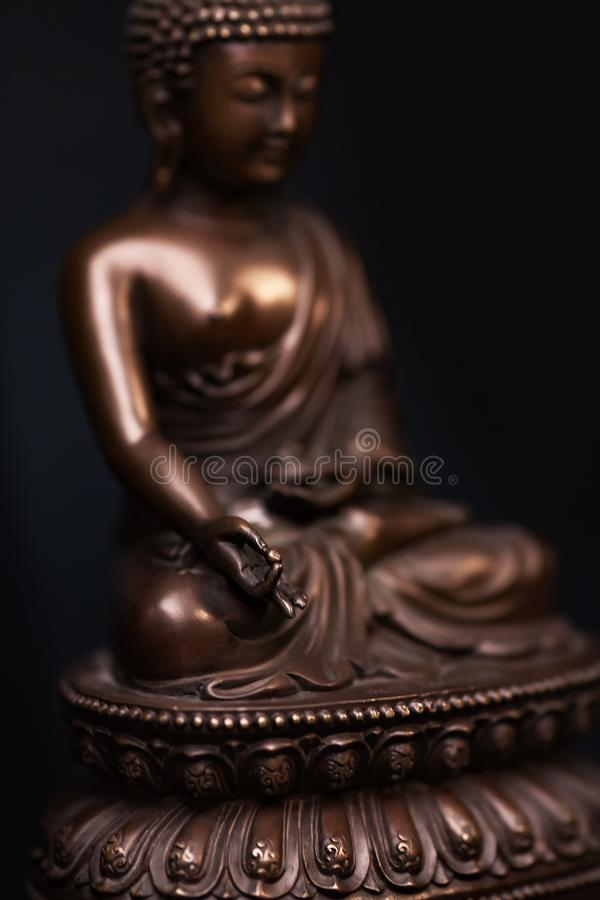 Buddha`s figure, brown color made of metal in a meditation pose royalty free stock photography