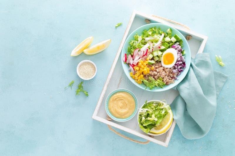 Buddha-Schüssel mit gekochtem Ei, Reis und Gemüsesalat von frischen Kopfsalat-, Rettich-, Gurken-, Mais-, Zwiebel- und Sesamsam stockbild