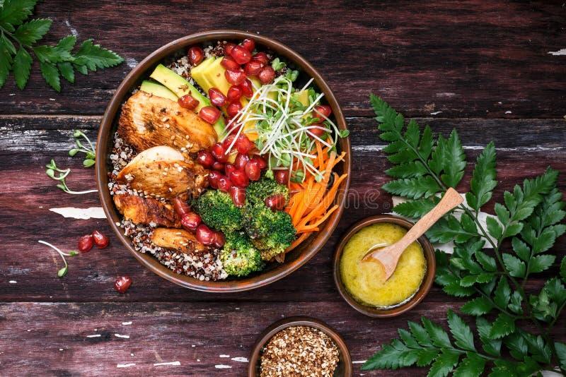 Buddha-Schüssel mit Quinoa, Avocado, gebratenem Huhn, Brokkoli, Karotten und Gelbwurz-Soße stockbilder
