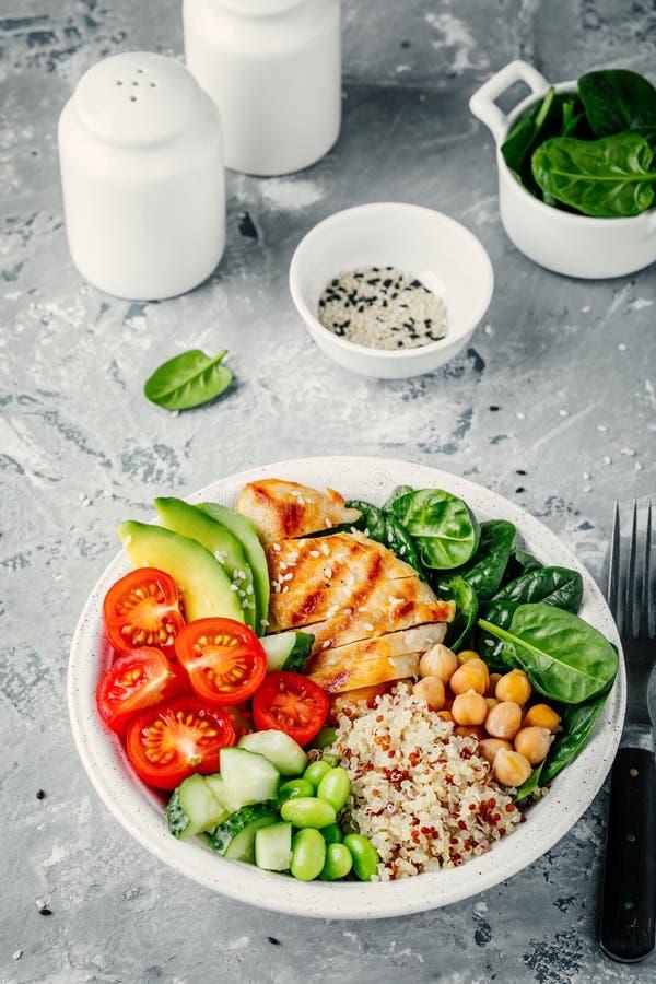 Buddha-Schüssel mit Spinatssalat, Quinoa, Kichererbsen, grillte Huhn, Avocado, Tomaten, Gurken, Samen des indischen Sesams stockbilder