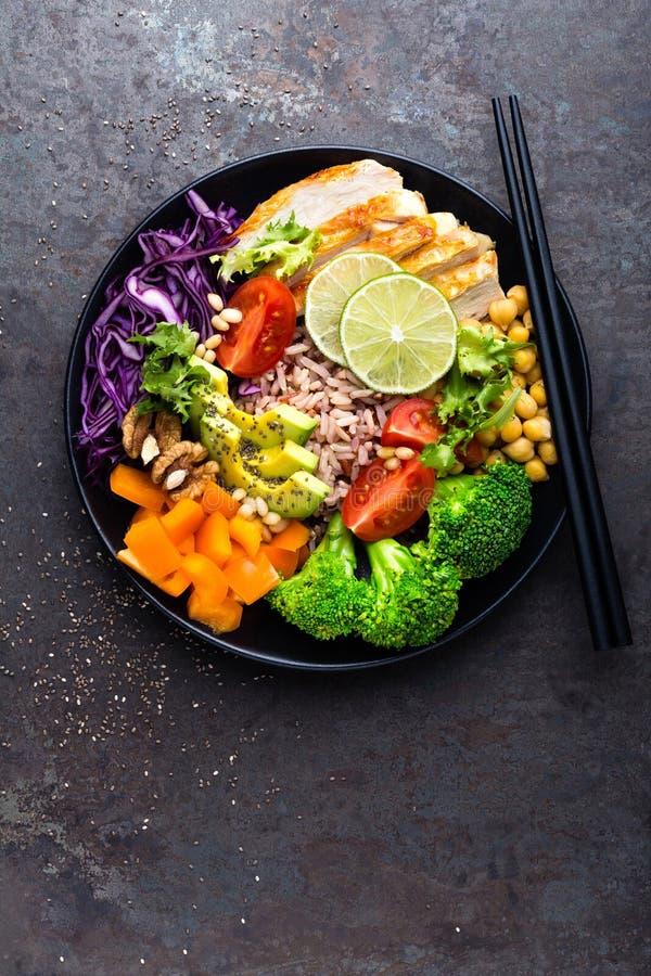 Buddha-Schüsselteller mit Hühnerleiste, Naturreis, Avocado, Pfeffer, Tomate, Brokkoli, Rotkohl, Kichererbse, frischer Kopfsalatsa stockbild