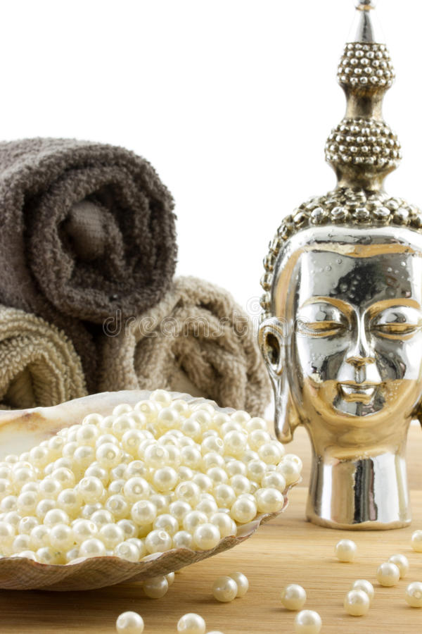 Buddha sculpture with towels and big shell. Buddha sculpture with towels and scallop shell filled with pearl beads on wooden surface stock image