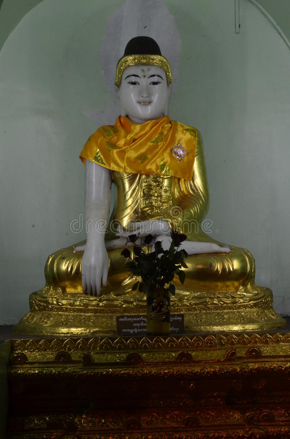 Buddha seated Statue at Shwedagon Pagoda. In Burmese style with red lip , eyebrow . The attitude of subduing Mara stock images