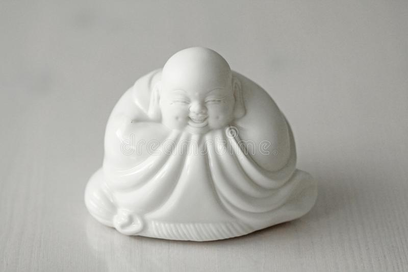 Buddha and Smile. Laughing Buddha. White Buddha Sits and Smiles royalty free stock photos