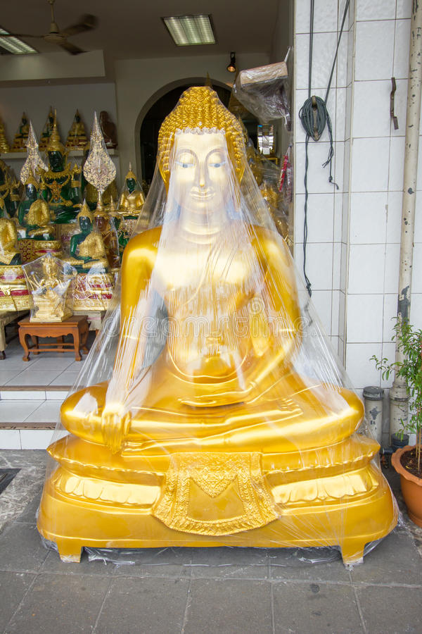Buddha som slås in i plast- arkivfoto