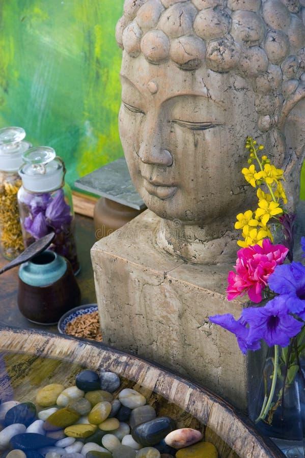 Buddha Spa. Buddha stone head with water basin and spa objects