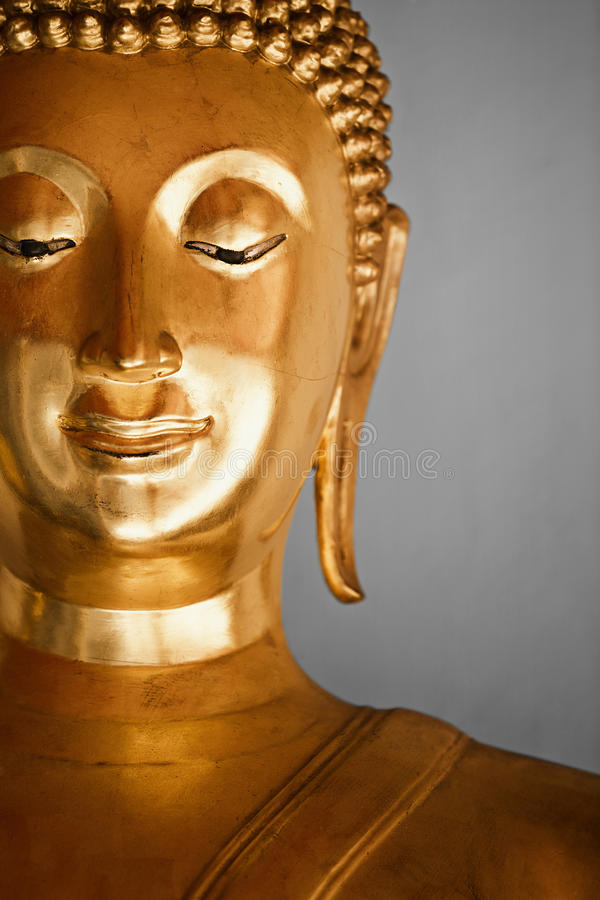 Buddha statue. Metal yellow traditional asian Buddha statue with soft smile, Thailand stock photo