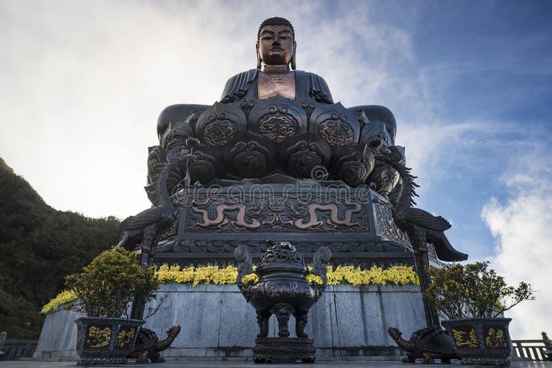 Buddha-Statue auf die Oberseite bei Sonnenuntergang in den Wolken Gro?e Buddha-Statue an der Spitze Fansipan-Berges, Sapa, Lao Ca lizenzfreies stockfoto