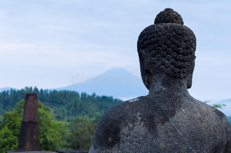 Buddha Statue at Borobudur. Buddha Statue overlooking mountain range in Borobudur temple, Central Java royalty free stock image