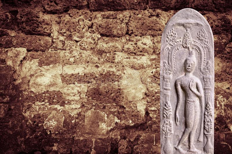 Buddha statue with brown bricks Wall background.  royalty free stock photo