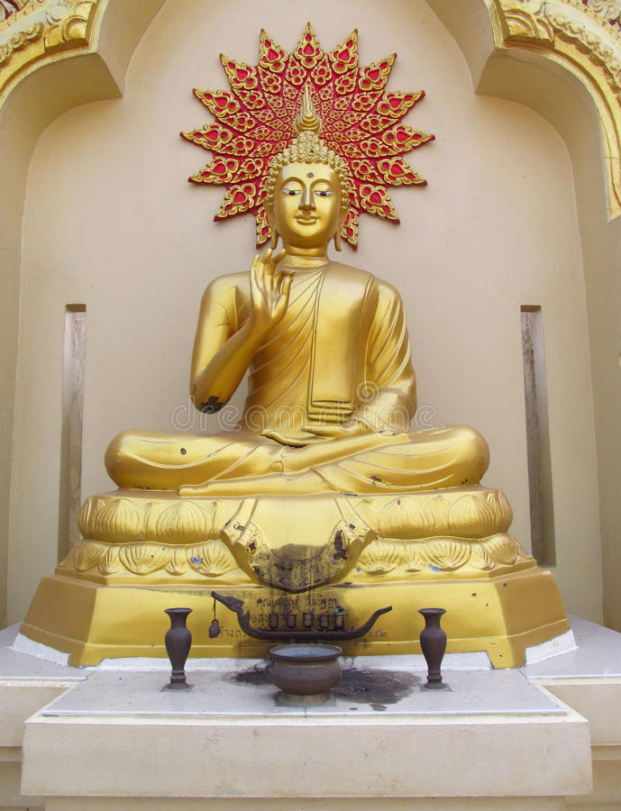 Buddha statue in Buddhist temple. Statue of seated Buddha coloured like gold. Buddha statue in a Buddhist temple. Sacred relic of Buddhism. Decorations and stock photography