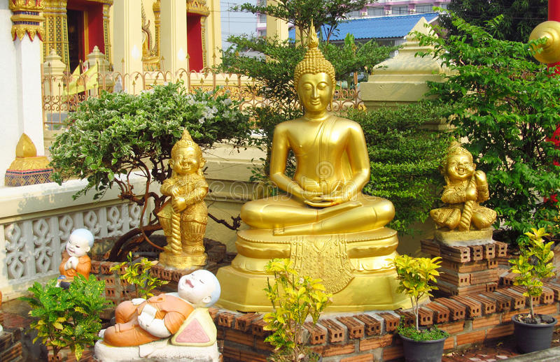 Buddha statue and laughing little monks near Buddhist temple stock images