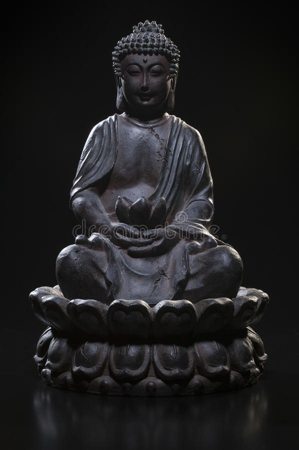 Buddha statue in lotus pose on black background. stock photos
