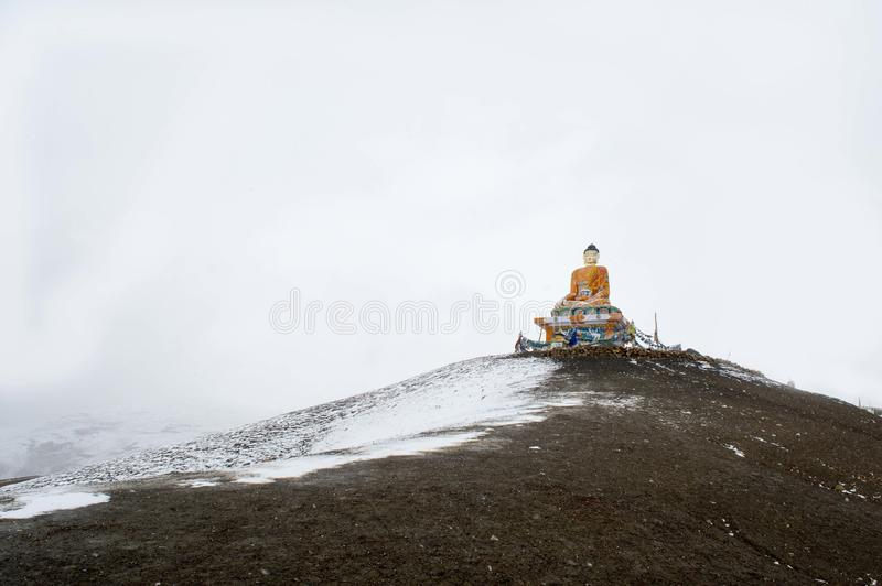 Buddha Statue - Snow Covered Landscape in Langza Village, Spiti Valley, Himachal Pradesh. The Spiti Valley is a cold desert mountain valley located high in the royalty free stock photos