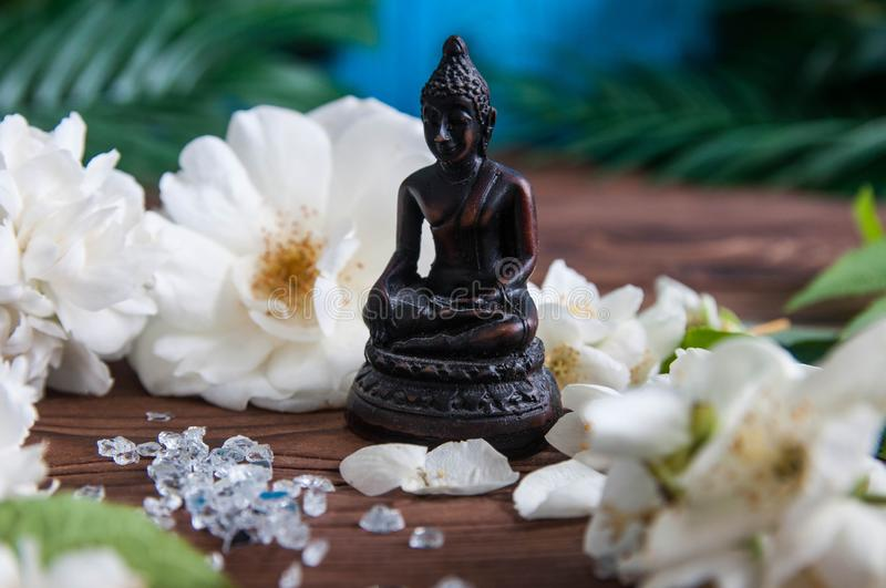 Buddha statue with white flowers, green leaves on wooden background. Concept of harmony, balance and meditation, royalty free stock photos