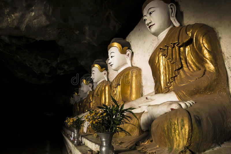 Buddha statues in a cave temple. In a row, golden, Hpan, Myanmar royalty free stock photo