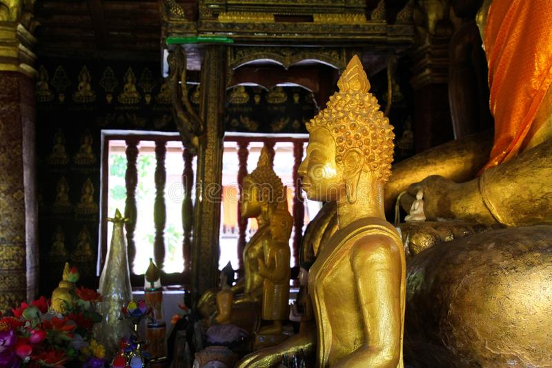 LUANG PRABANG WAT XIENG THONG, LAOS - DECEMBER 17. 2017: Buddha statues inside temple illuminated by natural sunlight stock image
