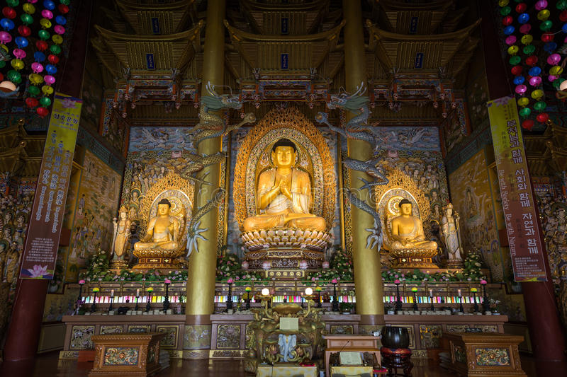 Buddha statues at the Yakchunsa Temple on Jeju Island. Dharma Hall and three golden Buddha statues inside the Yakchunsa (Yakcheonsa) Temple on Jeju Island in stock images