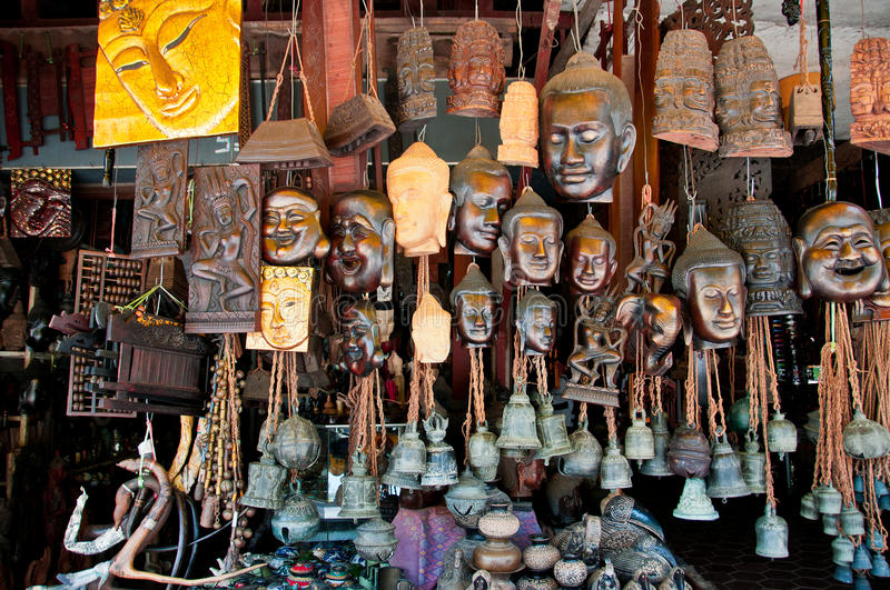 Buddhas and Bells. A shop display of hand carved buddha heads and old temple bells in Asia stock photography