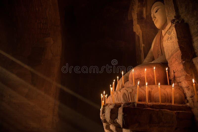 Buddhastaty inom pagoden med stearinljusljus under strålen av ljus arkivbilder