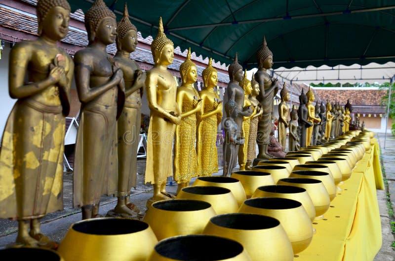 Buddhastaty och Allmosa-bunke av munken för folkdonation som ner sätts arkivfoto