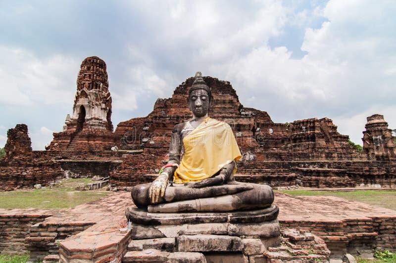 Buddhastaty och bruten pagod på Wat Mahathat fotografering för bildbyråer