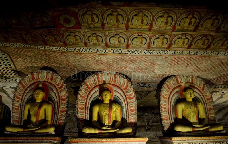 Buddhastatyer i den Dhyana Mudra positionen i Dambulla arkivfoto