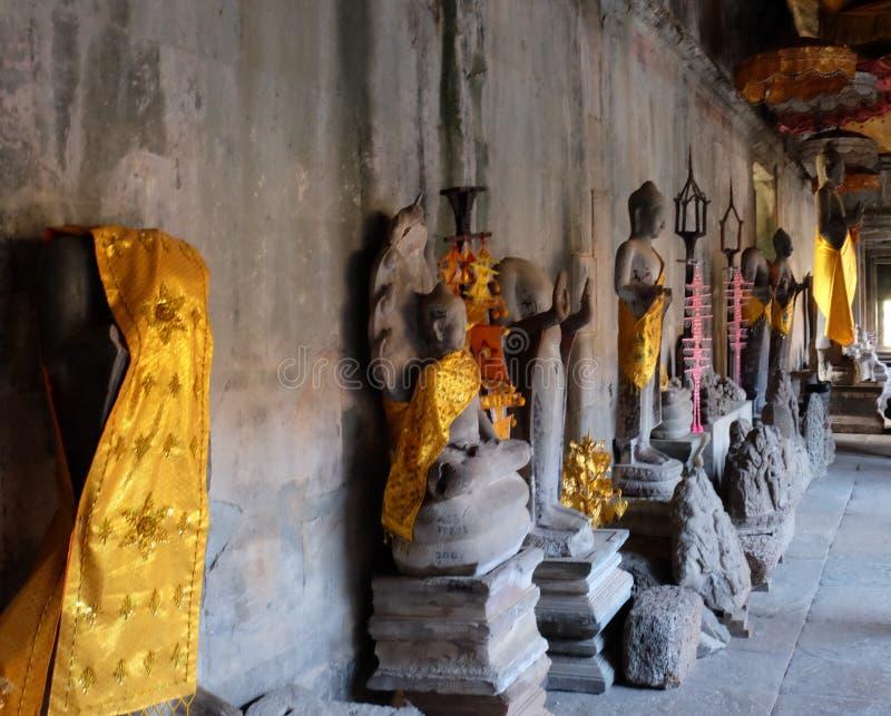 Buddhastatyer i guld- ämbetsdräkter står längs väggarna av en forntida tempel Ett ställe av religiös dyrkan Ett exempel av kloste arkivbild