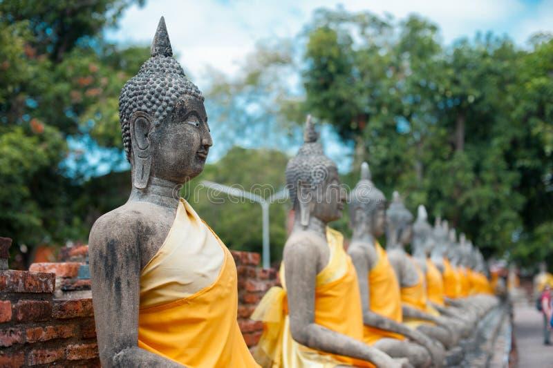 Buddhastatyer uppställda på den Ayutthaya världsarvet, Thailand Thailand är bekant som ett land av leendet arkivbild
