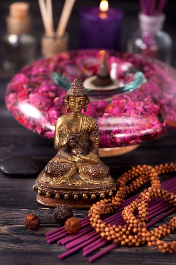 Buddhastatyn, nödvändiga oljor, rökelse klibbar aromatherapy begreppsbrunnsort royaltyfria foton