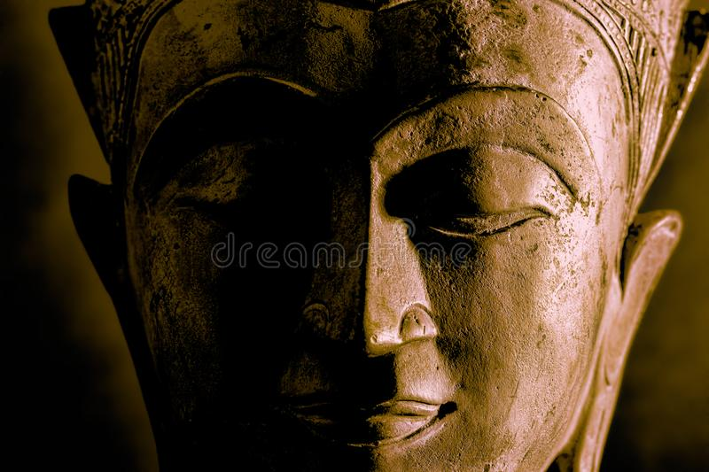 Buddhism. High contrast Buddha face statue close-up. Dramatic side light royalty free stock images