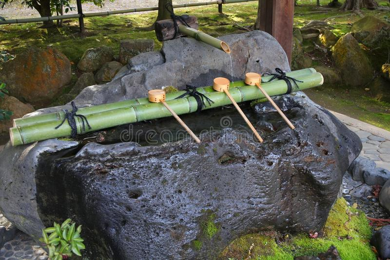 Buddhism purification. Japan culture - purification fountain with wooden ladles at a Buddhist temple (Ryoanji) in Kyoto royalty free stock images