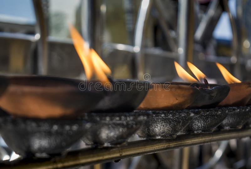 Buddhist altar with burning wooden cups royalty free stock images