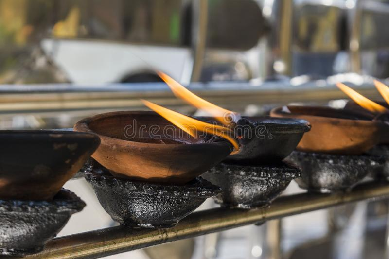 Buddhist altar with small burning wooden cups stock images