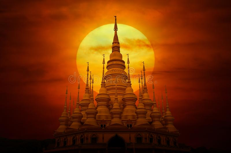 Buddhist architectural and sunset, mystery. Unique Buddhist temple and big sun solar in the background, red sky, mysterious atmosphere stock photos