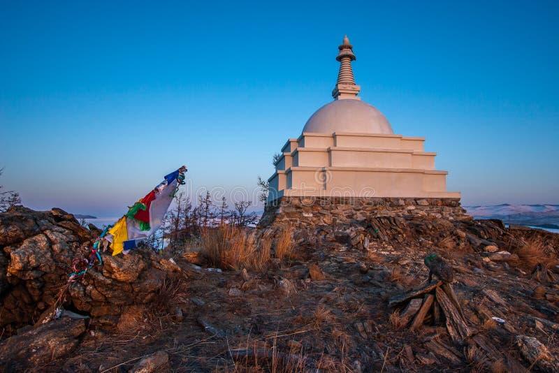 Buddhist big white stupa against the blue sky on the island of Ogoy on Lake Baikal. stock photos