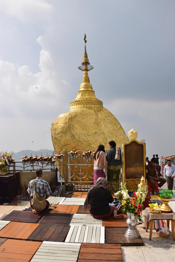 Buddhist devotees praying in front of the Golden Rock at Kyaiktiyo Pagoda stock image