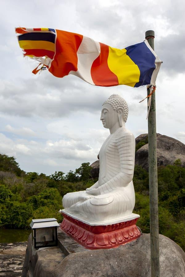 A Buddhist flag flies adjacent to a statue of Buddha. A Buddhist flag flies adjacent to a statue of Buddha at Madya Mandalaya near Panama in Sri Lanka. The royalty free stock photo