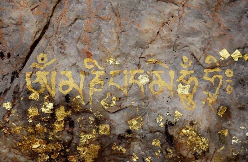 Buddhist Gold Mantra Painting on Stone stock image