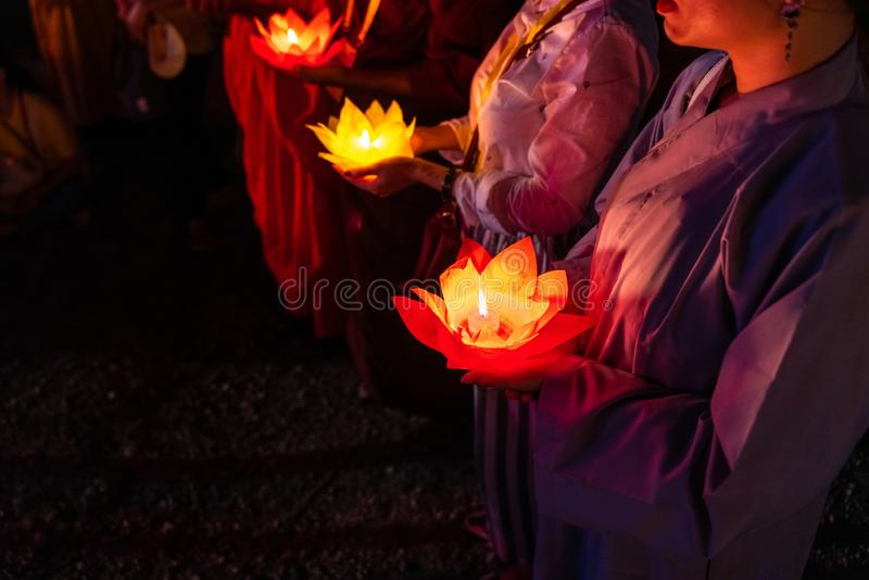 Buddhist hold lanterns and garlands praying at night on Vesak day for celebrating Buddha`s birthday in Eastern culture.  stock image
