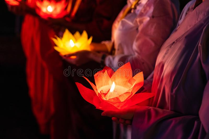 Buddhist hold lanterns and garlands praying at night on Vesak day for celebrating Buddha`s birthday in Eastern culture.  stock images